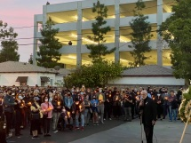 American Society of Cinematographers President Stephen Lighthill speaks at a vigil for Halyna Hutchins Sunday evening, as photographers document the gathering from a parking garage above.
